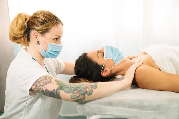 Короткий снимок женщины кавказской национальности, получающей физиотерапевтический массаж плеч, лежа на носилках в маске для лица из-за пандемии коронавируса covid 19
