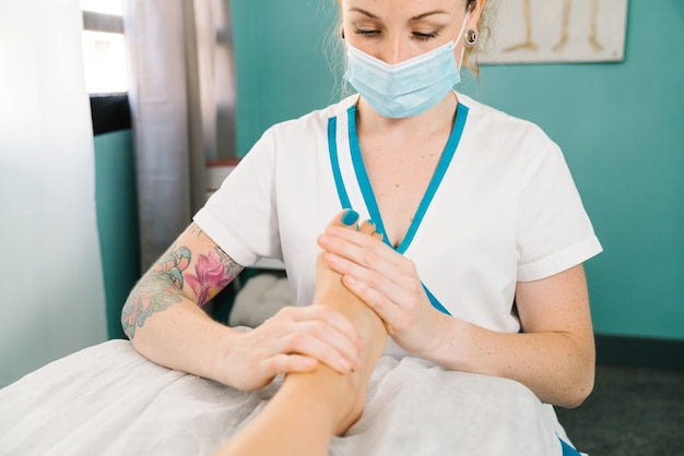 Short shot of professional caucasian woman giving a physiotherapeutic foot massage wearing a face mask due to the covid 19 coronavirus pandemic
