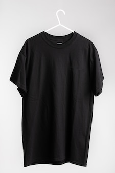 Short sleeve shirt on cloth hanger with white wall in the background
