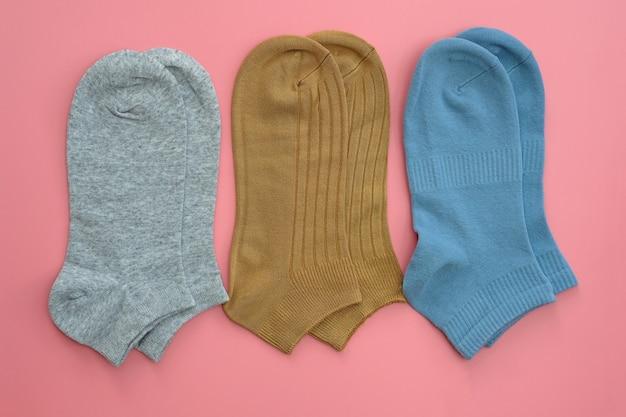 Носки короткие серого, коричневого и синего цвета на розовом фоне