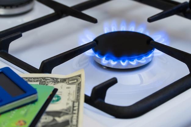 Дефицит и газовый кризис. деньги и калькулятор на фоне горящей газовой плиты