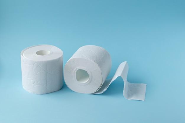 Концепция нехватки. два рулона туалетной бумаги на синем фоне, вид сверху. место для текста.