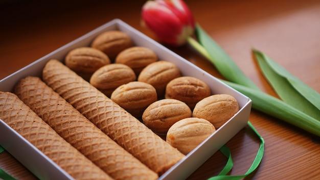 ショートブレッドクッキーとチューリップ。女性への贈り物。ロシアのお菓子-oreshkiクッキーとチューブ