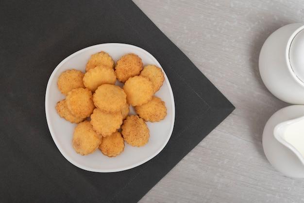 Песочное печенье на белом блюде сверху. домашнее печенье. хлебобулочные изделия. вид сверху. выпечка к чаю.