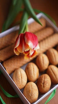 Shortbread cookies and tulips. gift to the woman. russian sweets - oreshki cookies and tubes - vertical photo - good format for stories
