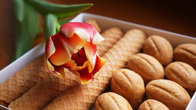 Shortbread cookies and tulips. gift to the woman. russian sweets - oreshki cookies and tubes