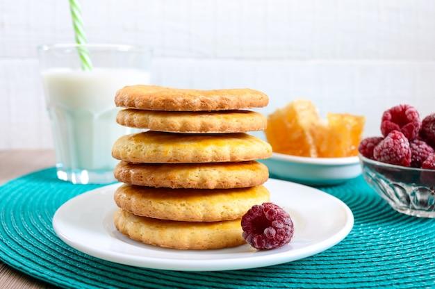 Песочное молочное печенье с молоком и медом. стопка печенья на тарелке.
