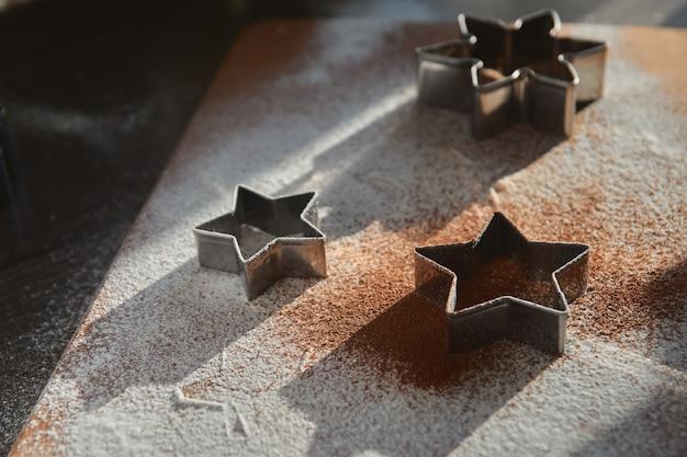 Песочное тесто для пряников раскатанное на деревянной доске. вырезание звезды. концепция новогодних традиций и процесс приготовления. печенье на темно-коричневом деревянном столе. создание семьи