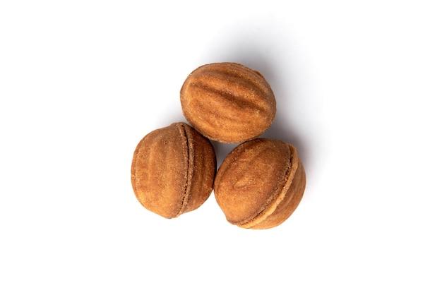 Песочное печенье в форме ореха с карамелью, изолированной на белом.