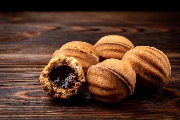 Песочное печенье в форме ореха с карамелью на темном деревянном столе