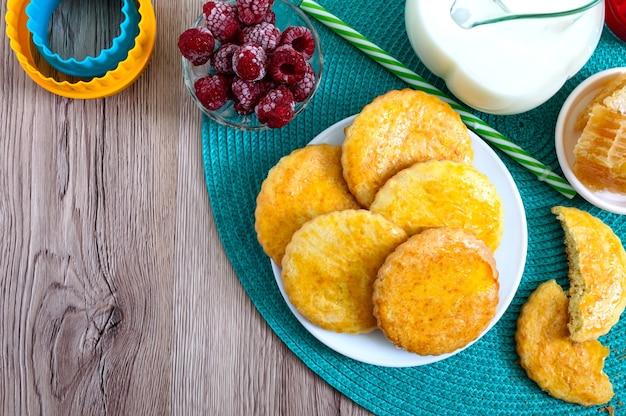 プレート上のショートブレッドミルククッキー、ミルクと蜂蜜。おいしい朝食。上面図。