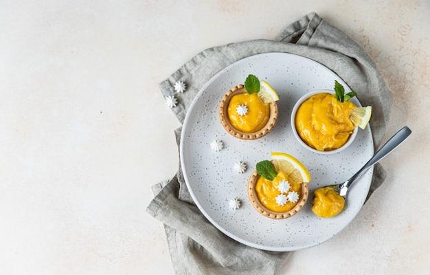 Shortbread mini tart with lemon curd mint and lemon slices and mini meringue
