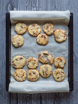 Shortbread with dates on a baking sheet is laid out on a dark wooden surface