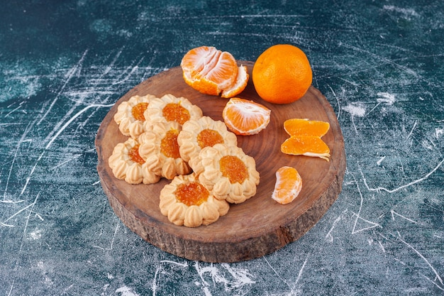 Shortbread with jam and peeled tangerine fruits placed on a colorful surface .