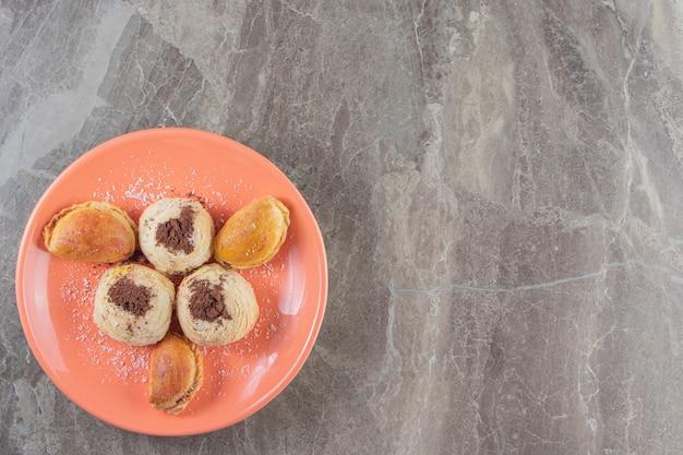 Frollini e cacao in polvere sui biscotti su un piatto sul blu.