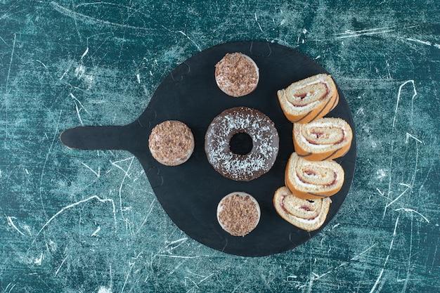 青いテーブルの上、まな板の上にショートブレッド、ドーナツ、スライスしたロールケーキ。
