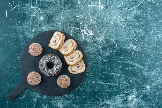 Frollini, ciambella e rotolo di torta a fette sul tagliere, sul tavolo blu.