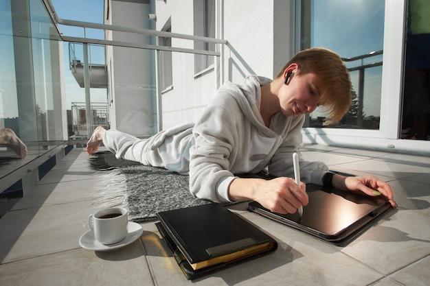 パジャマを着ている短髪赤毛の女の子のデジタルアーティストは日当たりの良いバルコニーに格子縞にあります。