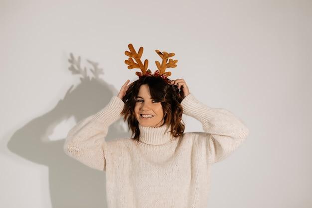 Короткошерстная женщина трогает свой рождественский головной убор модель в белом свитере позирует с милой улыбкой