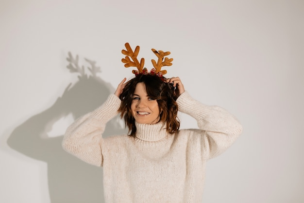 Shorthaired woman touching her christmas headwear model in white sweater posing with lovely smile