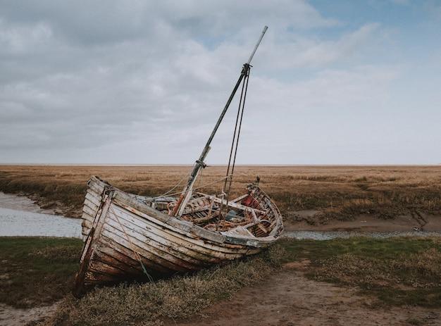 Inquadratura di una barca rotta abbandonata lasciata sulla riva del fiume circondata da un campo di grano