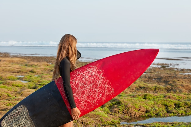 Shot of active sporty woman carries red surfboard with waxed surface