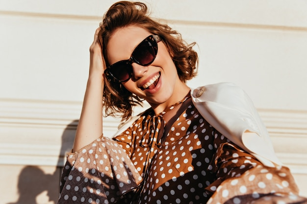 Shot of adorable pleased woman in black sunglasses. outdoor shot of refined curly lady expressing happiness.