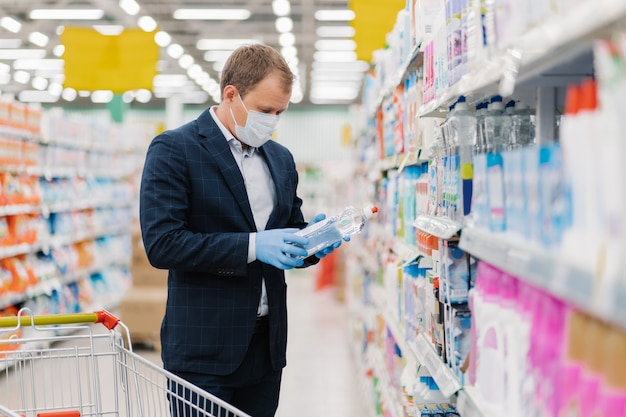 Shot of adult man chooses detergent in housekeeping store, reads label and instruction how to use product, wears medical mask and gloves during coronavirus pandemic, avoids risk to catch virus