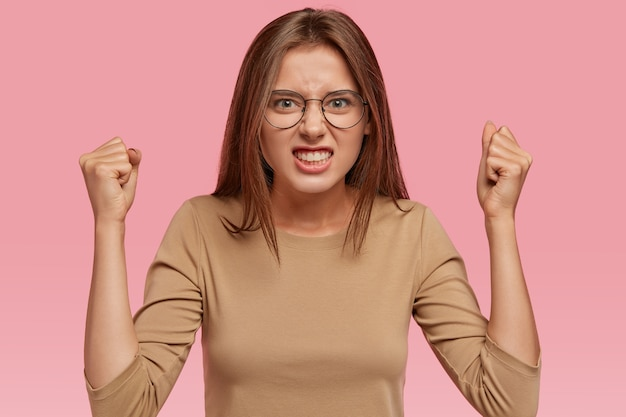 Shot of aggressive woman raises hands clenched in fists, argues with neighbours, looks intense and irritated, expresses irritation, wears beige sweater, isolated over pink wall. crazy girl