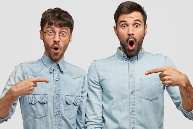 Shot of amazed bearded guys with stupefied expression point at each other with index fingers, wear denim shirts, opens mouthes widely, stand against white wall. friendship concept