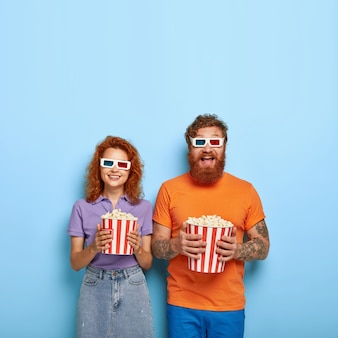 Shot of amused happy red haired boyfriend and girlfriend entertained in cinema, wear 3d glasses, watch funny comedy, eat popcorn from basket, spend free time together, enjoy hilarious movie