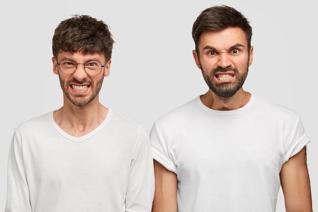 Inquadratura di uomini barbuti arrabbiati e furiosi, i colleghi stringono i denti per il fastidio, provano irritazione mentre ricevono molto lavoro e doveri dal capo, vestiti con magliette bianche casual. emozioni umane negative