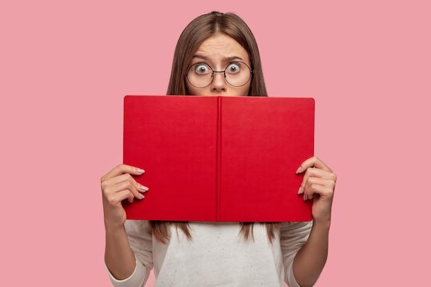 Inquadratura di ansiosa donna dai capelli scuri nasconde il viso con il libro, indossa occhiali rotondi, maglione bianco, legge informazioni sorprendenti, guarda con occhi pieni di paura, isolato su un muro rosa, si sente perplesso