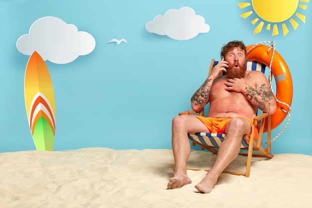 Shot of astonished bearded redhead man posing at the beach