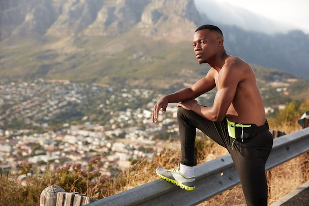 Shot of athlete man with dark healthy skin, has rest after physical exercises, keeps legs raised on traffic sign, has thoughtful expression, poses in moutains enjoys sport in open air. jogging concept