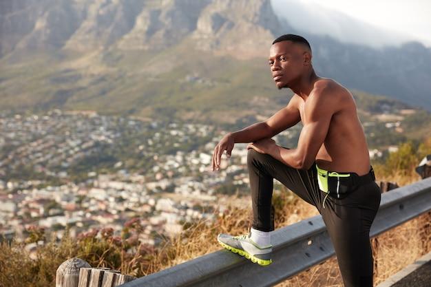 Colpo di atleta con pelle scura e sana, si riposa dopo esercizi fisici, tiene le gambe sollevate sul segnale stradale, ha un'espressione pensierosa, posa in montagna e gode di sport all'aria aperta. concetto di jogging