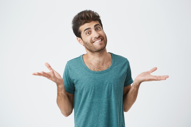 Shot of attractive bearded grinning man dressed in blue t-shirt, telling he doesnt know what to do. clueless and puzzled stylish student shrugging his shoulders expressing uncertainty. facial express