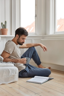 Colpo di attraente uomo intelligente che ama leggere il libro a casa si siede al pavimento vicino al letto, beve bevande calde fresche, ama il romanzo, si sente ispirato e rilassato, gode di un'atmosfera tranquilla. la letteratura ci sviluppa