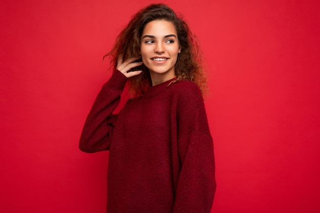 Shot of attractive happy smiling young woman wearing casual outfit standing isolated over colourful