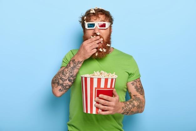 Colpo di attraente uomo dai capelli rossi guarda la telecamera attraverso gli occhiali del cinema