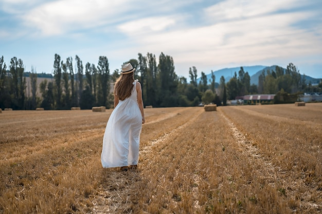 Shot of an attractive young peasant woman in a white dress in a dry field of straw