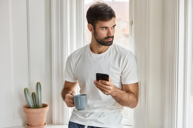 Shot of bearded caucasian man in white t shirt, holds mobile phone and mug of coffee, installs new application, enjoys free internet, focused aside, orders food in restaurant for dinner, drinks coffee