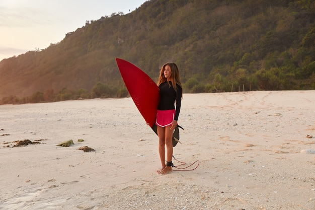 Shot of beautiful fit girl in waterproof clothes for surfing