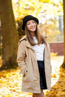 Shot of a beautiful happy smiling girl posing in an autumn forest