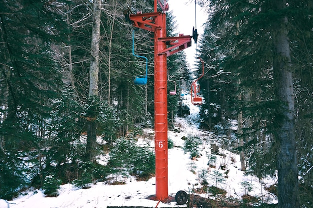 Colpo di bella vecchia piccola sciovia con sedie colorate, che si muove attraverso la foresta invernale in montagna