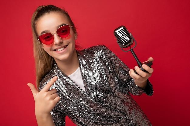 Shot of beautiful positive brunette female teenager wearing stylish shine jacket and red glasses