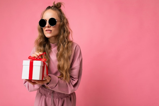 Shot of beautiful positive young blonde curly woman isolated over pink background wall wearing pink sport clothes and sunglasses holding gift box and unboxing surprise looking to the side. empty space