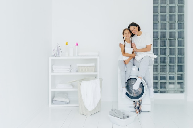 Shot of beautiful woman and his small daughter embrace and smile pleasantly, sit on washing machine, wash linen in laundry room, have friendly relationship, do laundry at home. housework concept