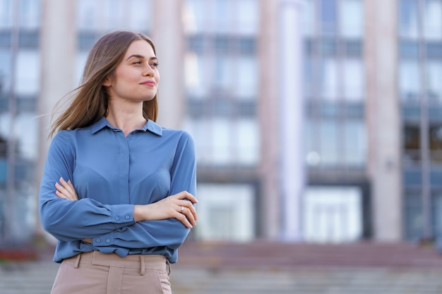 Shot of beautiful young businesswoman wearing blue chiffon shirt while standing on building in the street with folded arms.