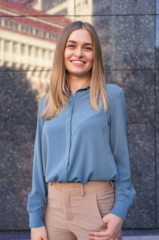 Colpo di bella giovane donna di affari che indossa camicia di chiffon blu mentre in piedi e in posa sul muro di marmo grigio